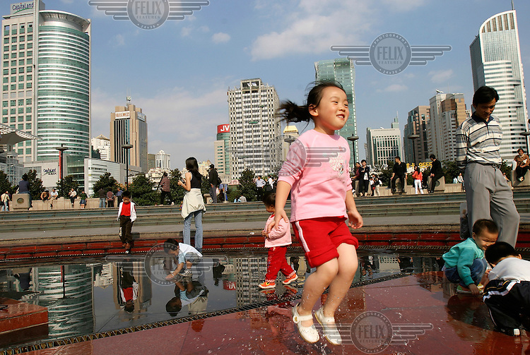 Children play in a dry fountain in People's Square.