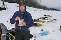 Robert Sorlie, in first place, eats a snack during  a break on the Yukon river at the Eagle Island checkpoint.  2005 Iditarod Trail Sled Dog Race.
