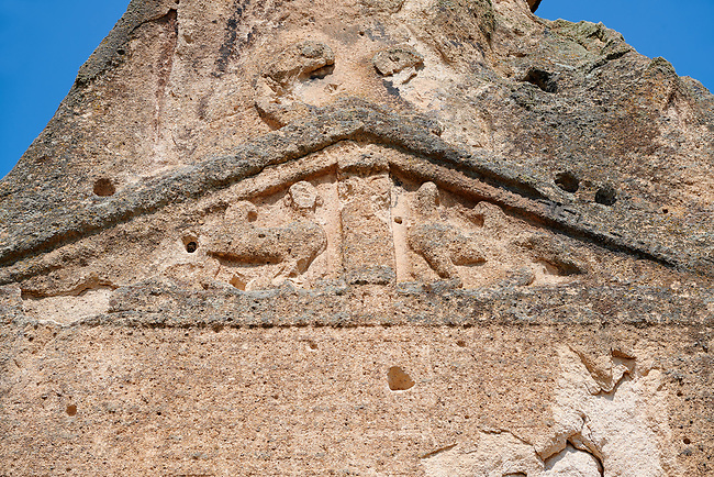 Close up of two sphinxes relief scul[ptures of the Phrygian temple of Aslankaya, 7th century BC. Phyrigian Valley, Emre Lake, near Doger, Turkey.<br /> <br /> On the triangular roof over the facade are two sphinxes (winged figures with the head of a human and the body of a lion), facing one another, take place. In the main facade, below, the sphinxes in a niche, a cult statue of Kybele or the Great Mother (vandalised and destroyed) was flanked by two lions. This main facade is ornamented with relief geometrical patterns.