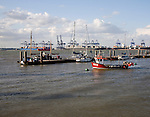 Boats in the harbour at Harwich, Essex, England with shipping activity at the Port of Felixstowe in the background