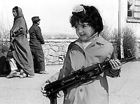 A girl plays with an unloaded AK-47 assault rifle in the Afghan capital Kabul on March 11, 1989.