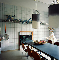 The dining room area was converted from a butcher's shop and still has the original wall tiles. The use of various shades of grey and blue soften the industrial feel of the room