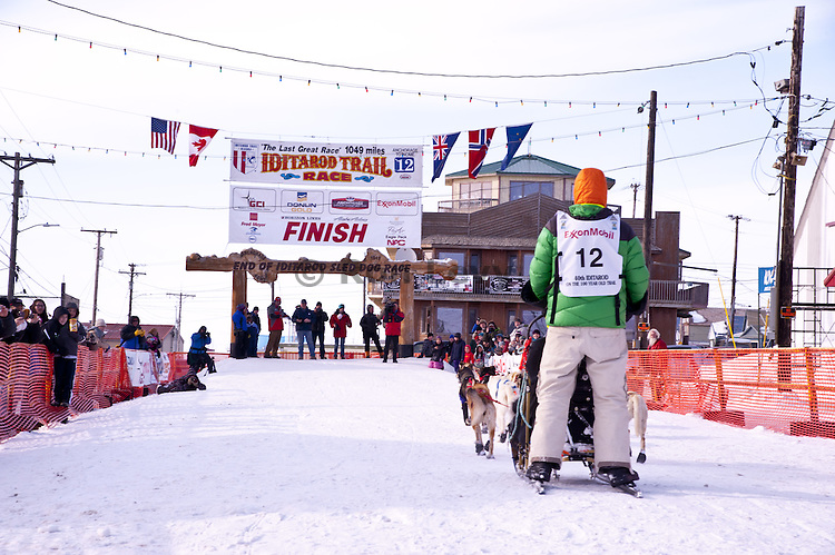 Musher Kelly Maixner arrives at the finish line in Nome, Alaska during Iditarod Dogsled Race, 2012
