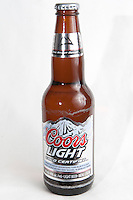 A Coors light beer bottle over a white background