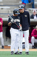 Wake Forest Demon Deacons head coach Tom Walter (16) gives instructions to Joey Rodriguez (7) during the game against the Florida State Seminoles at Wake Forest Baseball Park on April 19, 2014 in Winston-Salem, North Carolina.  The Seminoles defeated the Demon Deacons 4-3 in 13 innings.  (Brian Westerholt/Four Seam Images)