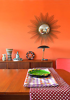 A 1950s metal lamp by Louis Christian Kalff beneath a sunburst mirror is a feature of this orange-painted dining room