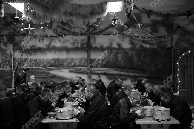 Prisoners have lunch against a background of a Russian rural scene with New Year decorations hanging from the ceiling.  Prison colony #7 outside of Novgorod in the Novgorod region south of St. Petersburg, Russia, December 15, 2008.