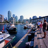 Vancouver, BC, British Columbia, Canada - Historic Wooden Steamboat in False Creek approaching Tourists on Dock on Granville Island, Granville Street Bridge and Yaletown Highrises in background