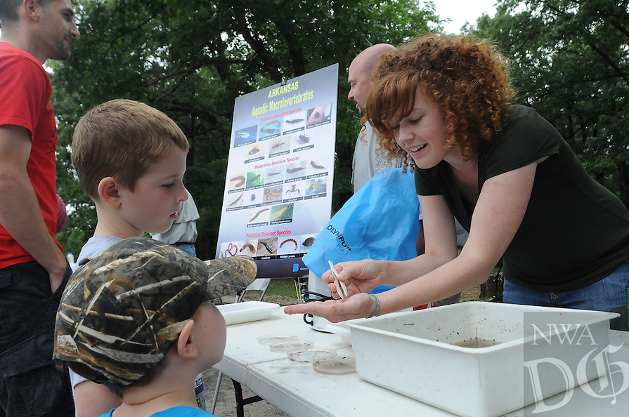 NWA Democrat-Gazette/ FLIP PUTTHOFF<br /> WAR EAGLE APPRECIATON<br /> Allyn Dodd (right) a University of Arkansas graduate students, gives a lesson on aquatic insects to Keaton Baltz, 6, and his brother, Brooks Baltz (in ball cap), 3, during War Eagle Appreciation Day on Saturday May 30 2015 at Withrow Springs State Park north of Huntsville. The event featured education exhibits, a shorline cleanup on part of the War Eagle River, and a performance by the musical duo, Still On The Hill, of songs they've written about Beaver Lake and the lake's watershed. A goal of the annual War Eagle Appreciation Day is to make people aware of the War Eagle and other streams in the Beaver Lake watershed and the need to keep them clean, said Dot Neely with the Beaver Water District. Beaver Lake is the primary drinking water source for Northwest Arkansas.