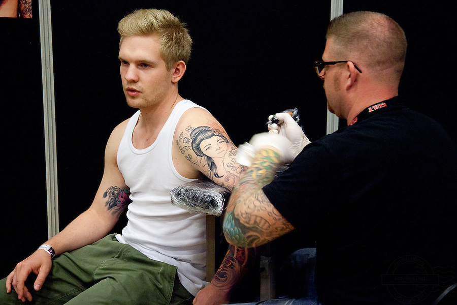 Tattoo Convention in Kolding 2011. Arranged by BodyMod.dk<br /> Young man getting tattoed on his arm. Japanese Geisha.