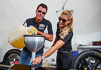 Aug 19, 2016; Brainerd, MN, USA; Papa Johns pizza founder John Schnatter (left) helps NHRA top fuel driver Leah Pritchett pour nitromethane racing fuel into the dragster during qualifying for the Lucas Oil Nationals at Brainerd International Raceway. Mandatory Credit: Mark J. Rebilas-USA TODAY Sports