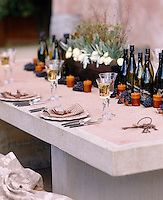 A concrete outdoor table laid out with a centerpiece of grapes candles wine and white flowers