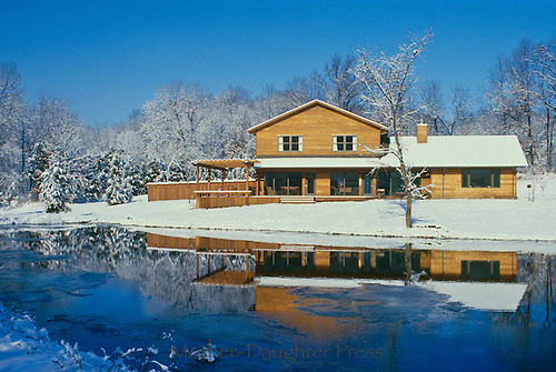 Cedar home reflected in ice covered lake on a sunny day with snow covered ground, Midwest USA