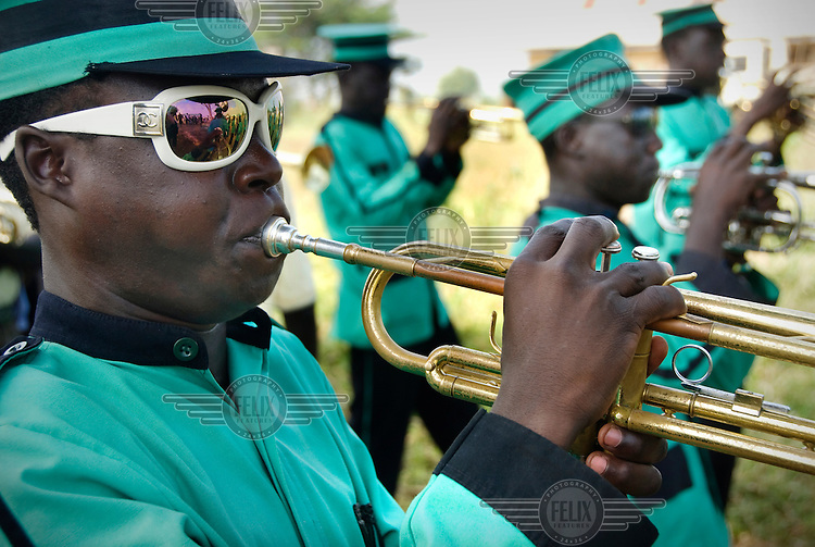 A brass band trumpet player wearing fake Chanel sunglasses.