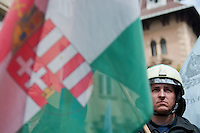 Protester is seen with the Hungarian flag during an anti-government rally in Budapest, Hungary on April 16, 2011..Thousands of Hungarians, including policemen and firefighters, on Saturday protested against the government's austerity measures. The government has launched a package of fiscal reforms to cut the budget deficit, including scrapping early retirement, which mostly affects law enforcement personnel.
