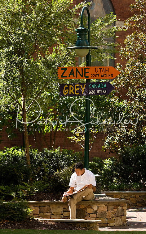 A professional businessman reads a magazine on the green in uptown Charlotte, NC.
