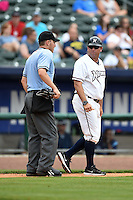 NW Arkansas Naturals manager Vance Wilson (13) gets an explanation on a call from umpire Derek Eaton during a game against the Corpus Christi Hooks on May 26, 2014 at Arvest Ballpark in Springdale, Arkansas.  NW Arkansas defeated Corpus Christi 5-3.  (Mike Janes/Four Seam Images)