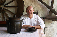 Traditional black earthenware pot with lid and handle and decoration and bowl called cereme used for cooking food. The black colour comes from the production process. The owner of the restaurant in traditional white shirt. Tradita traditional restaurant, Shkodra. Albania, Balkan, Europe.