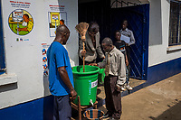 """MONROVIA, LIBERIA - FEBRUARY 16: Vice principal, Venoria Crayton, mixes a solution of chlrine for students to wash their hands with, on the first day of school, since schools closed due to the Ebola outbreak 6 months ago, at the C.D.B. King Elementary School on February 16, 2015 in Monrovia, Liberia. Ebola destroyed and devastated our land,'' Venoria Crayton, the vice principal, told her pupils. """"It brought us sadness, it brought us pain. Some of your neighbors died, right? Some of your neighbor's children died, right? But you are here."""" Though Ebola cases have receded into the single digits in Liberia, lingering fear and a depressed economy have dampened the turnout at schools. Many have yet to reopen, having failed to meet the minimum requirements put in place to prevent the transmission of the virus. Many of those that have reopened – like C.D.B. King, which, though located in the center of the capital, lacks electricity and running water, and has only a few toilet stalls for a student population that numbered 1,000 before Ebola — are struggling.<br /> Daniel Berehulak for The New York Times"""