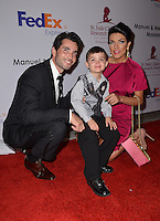 MIAMI, FL - MAY 19: Khotan and Candela Ferro pose with a child at the St. Jude Angels & Stars Gala at JW Marriott on May 19, 2012 in Miami, Florida.  (photo by: MPI10/MediaPunch Inc.)