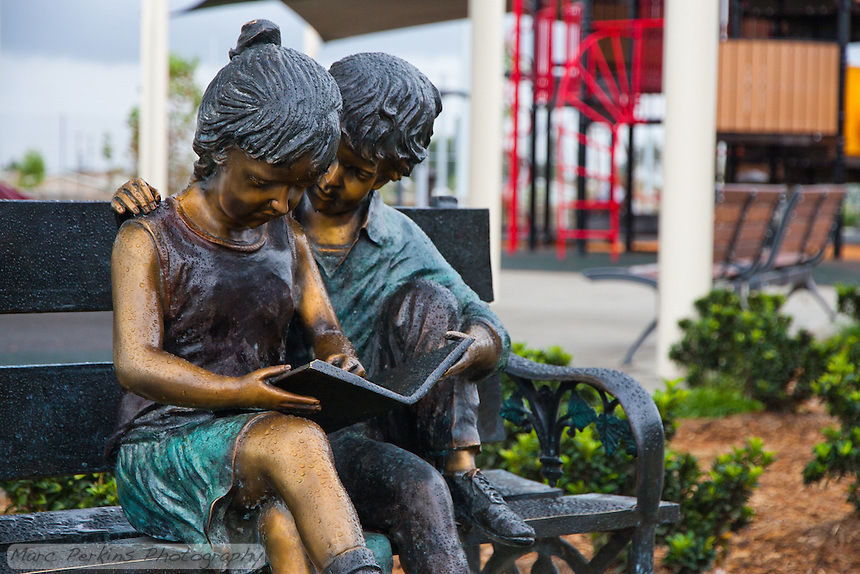 The gorgeous sculpture of two children reading a book on a park bench at Stanton Central Park's children's play area, seen on a rainy day with the water tower play structure in the background.  The children are covered in raindrops.