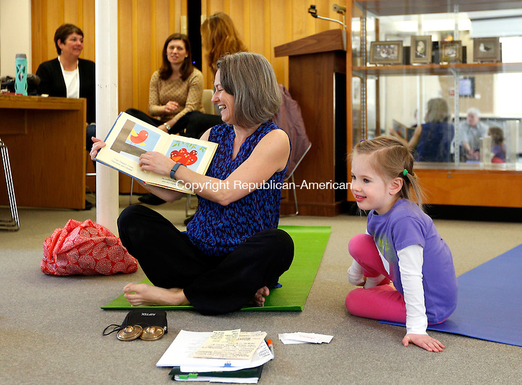 """Woodbury, CT- 08 March 2016-030816CM04-  Molly McEvoy, 3 of Southbury, right, listens in as Kathleen McGowan reads """"Pepito the Brave"""" by Scott Beck during a yoga and story time event at the Woodbury Public Library on Tuesday.  The program which will run on Tuesday mornings, will be held for three more weeks.  To sign up, contact the Woodbury Public Library at (203) 263-3502.  Christopher Massa Republican-American"""