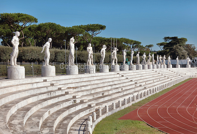 Stadio dei Marmi or Stadium of the Marbles, a stadium designed c. 1928 by Enrico Del Debbio and inaugurated 1932, at the Foro Italico, Rome, Italy. The stadium has Carrara marble steps lined by 59 marble statues of athletes in classical style. The Foro Italico or Foro Mussolini is a sports complex built 1928-38 in Fascist style by Enrico Del Debbio and Luigi Moretti, inspired by Roman forums. Fascist architecture developed in the late 1920s and 1930s, as a modernist style in times of nationalism and totalitarianism under Benito Mussolini. It is characterised by large, square, symmetrical buildings with little or no decoration, often inspired by ancient Rome and designed to convey strength and power. Picture by Manuel Cohen