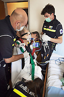 Switzerland. Canton Ticino. Mezzovico. A senior man is carried seated will be brought by ambulance to the hospital for medical examinations. The elderly man is suffering from severe respiratory problems. The emergency doctor Daniele Speciale (C) with beard and glasses is working with three paramedics. They all work for the Croce Verde Lugano. They wear blue uniforms, medical gloves and surgical masks. The man (R) and the woman (R) are professional certified nurses, the bald man (L) is a volunteer specifically trained in emergency rescue. The senior citizen has a mask on his face and receives oxygen from a medical ventilator carried by the doctor. A medical ventilator (or simply ventilator in context) is a mechanical ventilator, a machine designed to move breathable air into and out of the lungs, to provide breathing for a patient who is physically unable to breathe, or breathing insufficiently. The Croce Verde Lugano is a private organization which ensure health safety by addressing different emergencies services and rescue services. Volunteering is generally considered an altruistic activity where an individual provides services for no financial or social gain to benefit another person, group or organization. Volunteering is also renowned for skill development and is often intended to promote goodness or to improve human quality of life. Medical gloves are made of different polymers including latex, nitrile rubber, polyvinyl chloride and neoprene. 14.01.2018 © 2018 Didier Ruef