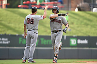 Catcher Sam Huff (27) of the Hickory Crawdads is greeted by manager Matt Hagen (39) after hitting a home run in Game 1 of a doubleheader against the Greenville Drive on Wednesday, July 25, 2018, at Fluor Field at the West End in Greenville, South Carolina. Greenville won, 4-1. (Tom Priddy/Four Seam Images)
