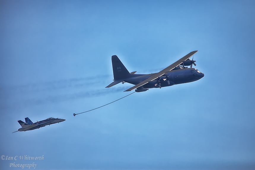 A CF-18 Hornet takes part in a refuelling demo with a CC-130 Hercules tanker at the Canadian International Air Show in Toronto.