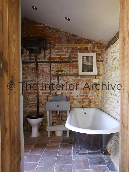 Rough, exposed brick walls and stone-paved floors have been juxtaposed in this bathroom to achieve the pleasingly rustic effect