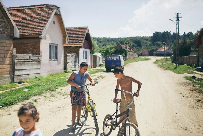 Drei Kinder auf der Strasse im Romaviertel von Rusciori, rechts Remus Lakatar. Europa, Rumaenien, Rusciori den 25. Juli 2015
