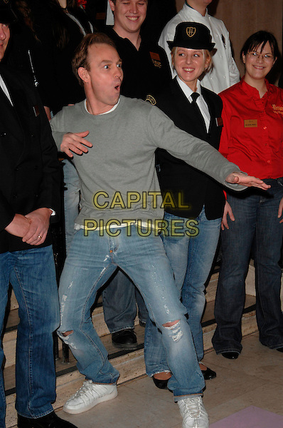 JASON DONOVAN.Genes For Jeans Charity Day - Photocall, Harrods, London, UK..February 22nd, 2007.full length ripped torn posing hands funny face grey gray top.CAP/CAN.©Can Nguyen/Capital Pictures