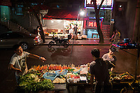 Streetside shaokao cooks work on Tiyu Road in central Yuzhong district, Chongqing, China. Shaokao is a style of barbecue in which patrons choose a variety of raw meats and vegetables to have spiced and cooked on a barbecue. In Chongqing, most shaokao cooks then mix all of the ingredients together after barbecuing and add garlic, green onions, hot peppers, and other flavors. The Tiyu Road is lined by streetside shaokao and hotpot restaurants.