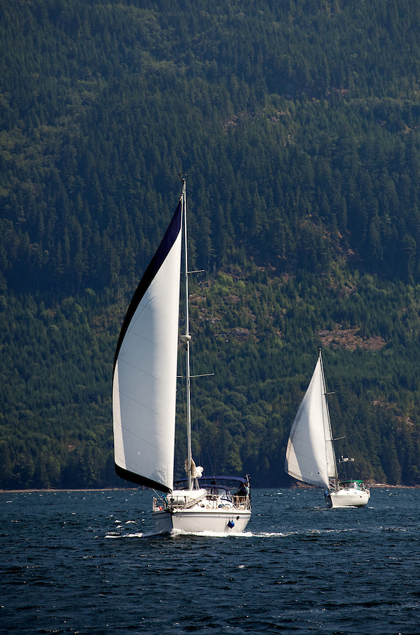 These two sailboats are seen transiting Jervis Inlet on a warm summer day.