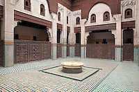 Internal courtyard of the Bou Inania Madrasa or religious school, founded in 1350 by the Marinid ruler Abu Inan Faris, Meknes, Meknes-Tafilalet, Morocco. The courtyard with its central fountain is decorated with zellige tiles in geometric patterns, carved stucco and cedar wood and is flanked by carved screens. Meknes is a fortified Imperial city redeveloped under Sultan Moulay Ismail, 1634-1727, as Morocco's political capital. Picture by Manuel Cohen