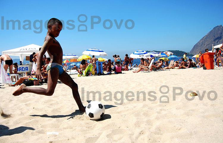 Menino jogando bola na praia do Flamengo, Rio de Janeiro, Brasil.