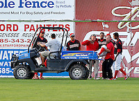 Batavia Muckdogs outfielder Roberto Reyes #4 is helped onto the back of a cart by trainer Mike Petrarca and strength coach Jake Roy as (L-R) David Medina, Romulo Ruiz, and Victor Encarnacion look on during the second game of a doubleheader against the Mahoning Valley Scrappers at Dwyer Stadium on August 22, 2011 in Batavia, New York.  Mahoning Valley defeated Batavia 11-3.  (Mike Janes/Four Seam Images)