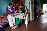 Video Volunteer videojournalist Niru J. Rathod, 24, shows some pictures to her sister Kailash (left), 19, who works at home as a seamstress in Surendranagar, Gujarat, India on 14 December 2012. While Niru's sisters have become seamstresses or housewives, Niru, the 8th child in a family of 11 girls born to a Dalit construction worker, has been using videography for social change since 2006. She shoots and produces her own short documentaries and is a committed video activist, having conducted hundreds of village video screenings where she also speaks to thousands of men, shattering their ideas about what a woman and a Dalit can do while bringing massive changes to the communities she documents. Photo by Suzanne Lee / Marie Claire France