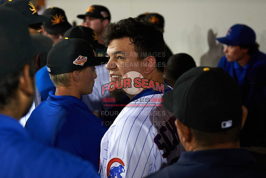 Mesa Solar Sox designated hitter Kyle Schwarber (66), of the Chicago Cubs, looks back smiling as players and staff huddle around a tablet showing the MLB playoff game with two outs in the bottom of the ninth inning against the Los Angeles Dodgers during a game against the Salt River Rafters on October 22, 2016 at Sloan Park in Mesa, Arizona.  It was the first game action for Schwarber who was injured April 7th and underwent surgery to repair two ligament tears in his left knee.  Salt River defeated Mesa 7-2.  (Mike Janes/Four Seam Images)