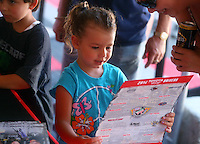 Jul. 26, 2014; Sonoma, CA, USA;  A young NHRA fan looks at her autographed Hero Card during qualifying for the Sonoma Nationals at Sonoma Raceway. Mandatory Credit: Mark J. Rebilas-