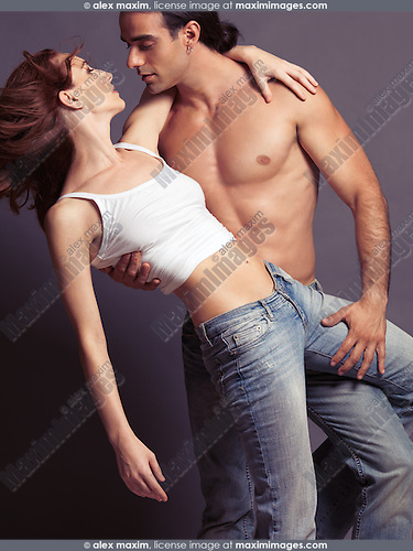 Artistic portrait of a sexy young couple dancing, young man with bare torso and young woman in jeans and tank top isolated on gray background