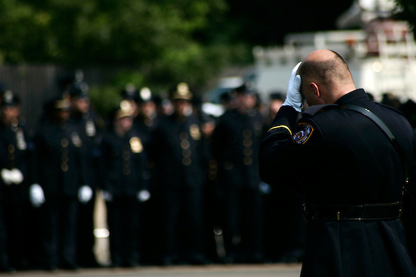 Thousands of police officers and military turned out for the funeral of James McNaughton, the first NYPD officer killed in the war in Iraq. An NYPD officer hangs his head as the honor guard assemble.