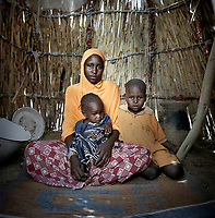 Tchelou Bossomi, 20, and her daughter Khalfoumi, 18 months and son Abba, 4, in an unnamed IDP camp on the outskirts of Meme. <br /> <br /> Armed men entered Tchelou's village at night while she was asleep. Those who were outside were shot at, so they fled. Her brothers were killed and three teenage were girls kidnapped. They walked for two days to reach safety. <br /> <br /> 'When we first arrived here we slept under trees in the village. Then people came and brought us to this camp. We have been here for nine months.<br /> <br /> 'The major problem is food and the food that is given to us gets finished very quickly. We have to beg when the food gets finished. We didn't used to have to do that. Sometimes you have to put shame aside. You know you're hungry, you know your kids are hungry.'