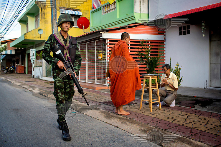 A soldier from the 23rd Battalion of the Thai Army provides security as monks from the Nopawong Saram Temple collect alms on their morning rounds in Pattani. /Felix Features