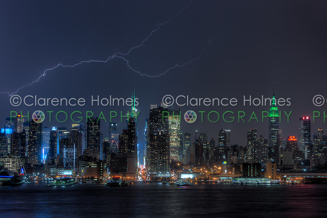 A forked lightning bolt illuminates the night sky behind the skyline of New York City during a summer thunderstorm on Friday, August 17, 2012.  The Empire State Building was illuminated in green lights in celebration of Eid-al-Fitr.