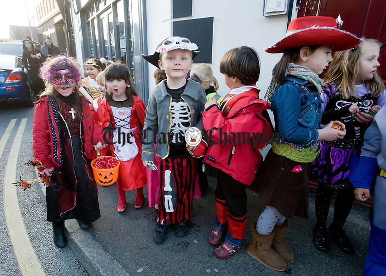 Ennis National School children depart with their treats after enjoying a visit to The Clare Champion Offices on Barrack street, as part of their annual Halloween Hobble. Photograph by John Kelly.