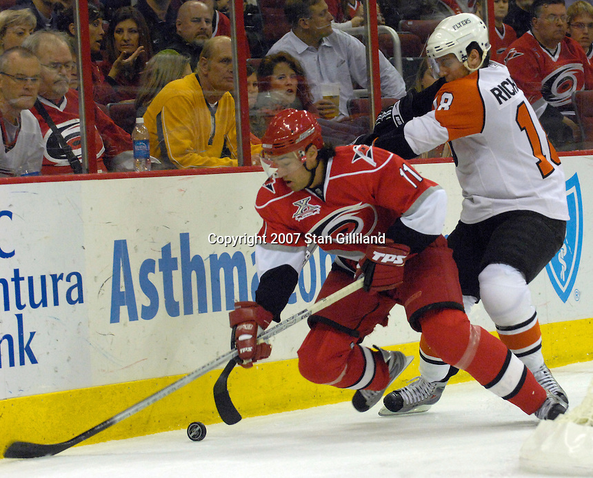 The Carolina Hurricanes' Justin Williams (11) is pushed by the Philadelphia Flyers' Mike Richards (18) during their game Wednesday, Nov. 21, 2007 in Raleigh, NC. The Flyers won 6-3.