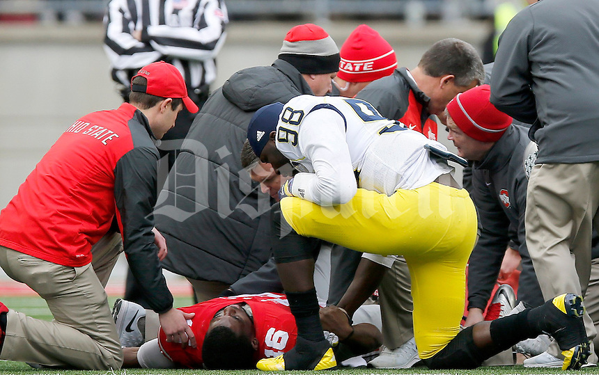 Michigan Wolverines quarterback Devin Gardner (98) comes over to talk to Ohio State Buckeyes quarterback J.T. Barrett (16) after his injury during the fourth quarter of the NCAA football game against Michigan at Ohio Stadium on Saturday, November 29, 2014. (Columbus Dispatch photo by Jonathan Quilter)