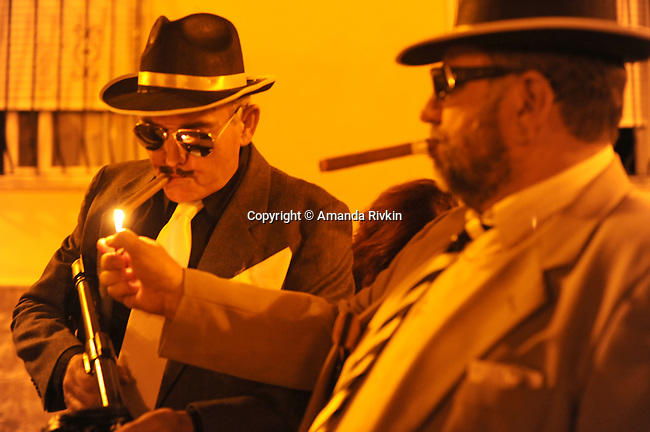 A man dressed as 1930s Chicago-style mafioso lights a friends cigar in the main square during the Costume Night celebration as part of the municipal fiestas in Costur, Spain on August 17, 2009.